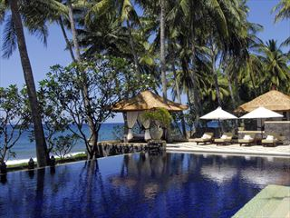 Swimming pool and sun loungers at Spa Village Resort Tembok, Bali