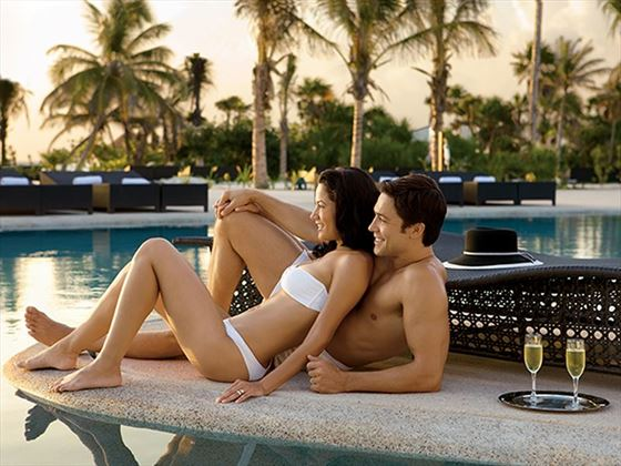 Couple relaxing by the pool at Secrets Maroma Beach Riviera Cancun