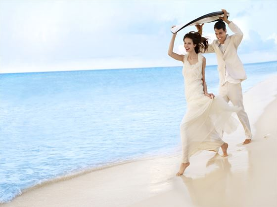Bride & Groom running on the beach