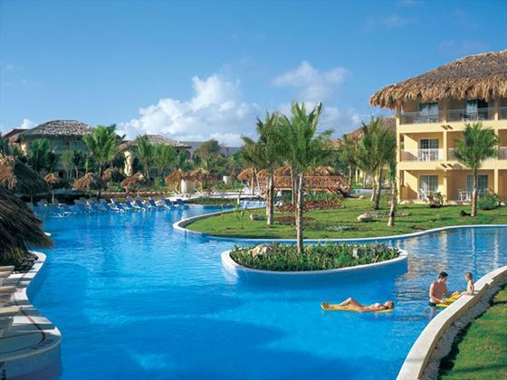 The main pool surrounded by chaise lounges and swim-out suites.