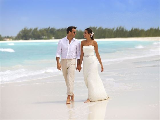 Newlyweds strolling along the beach