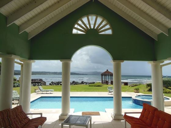 The lovely covered veranda leading to the sun terrace and pool with ocean views