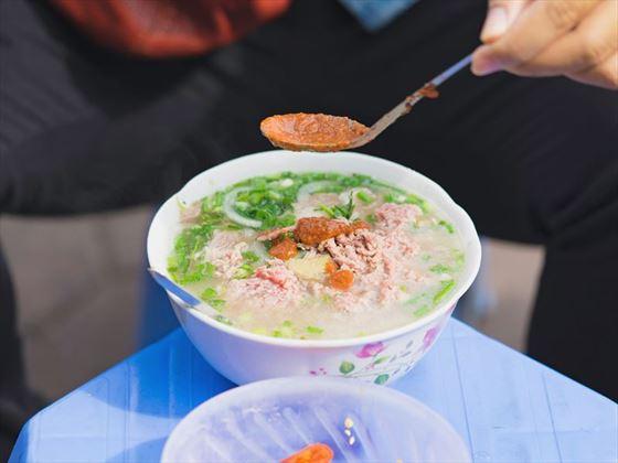 Soup server by Hanoi street vendor